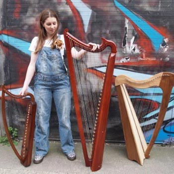 Young woman choosing between different types of harp