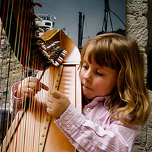 A small child learning the harp