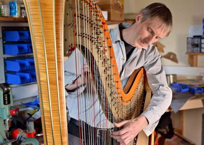 Harpmaker regulating a concert harp