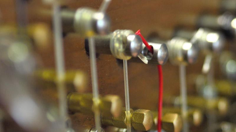 Winding a harp string round the tuning pin